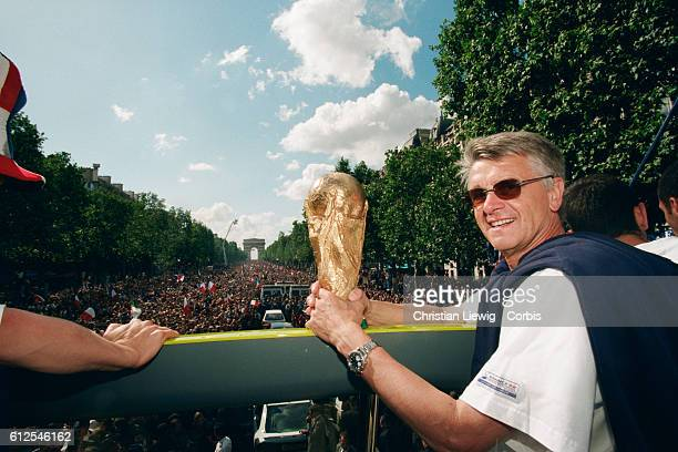France's head coach Aime Jacquet of France's 1998 FIFA World Cup squad with the team's trophy during a parade on the Champs Elysees celebrating their...