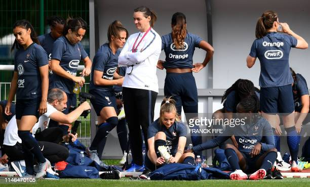 France's head coach Corinne Diacre stands next to France's players preparing during a training session in ClairefontaineenYvelines on May 27 as part...
