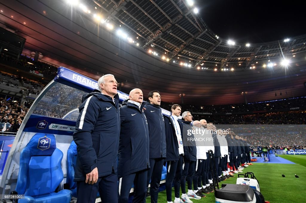 France's head coach Didier Deschamps and staff members sing the national anthem pictured during the friendly football match between France and Colombia at the Stade de France, in Saint-Denis, on the outskirts of Paris, on March 23, 2018. /