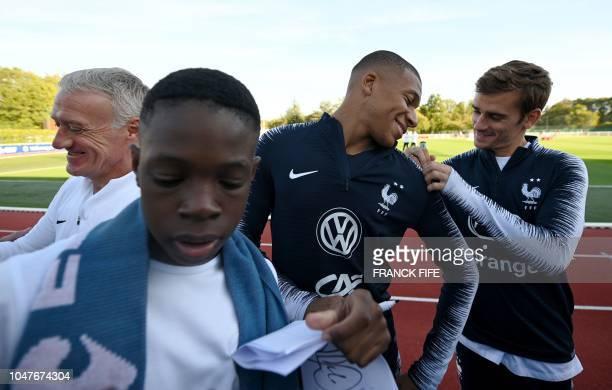 France's head coach Didier Deschamps, France's forward Kylian Mbappe ande France's forward Antoine Griezmann sign autographs before a training...