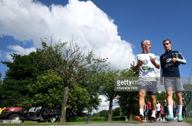 France's head coach Didier Deschamps speaks with France's forward Antoine Griezmann before a training session in ClairefontaineenYvelines on May 30...