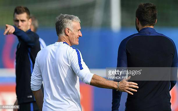 France's head coach Didier Deschamps speaks with France's forward Andre Pierre Gignac at the end of a training session of France's national football...