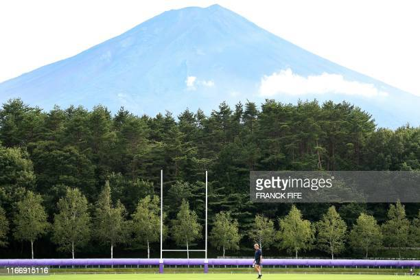 France's head coach Jacques Brunel walks on the pitch ahead of a training session at the Fuji Hokuroku Park in Fujiyoshida on September 9 where the...