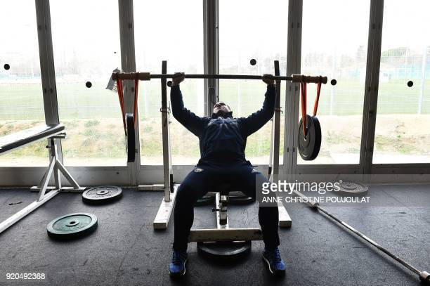 France's hook and captain Guilhem Guirado lifts weights during a training session along with players of the French national rugby union team on...