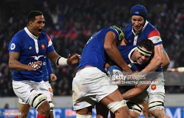 France's hooker Guilhem Guirado celebrates with teammates after scoring a try during the international rugby union test match between France and...