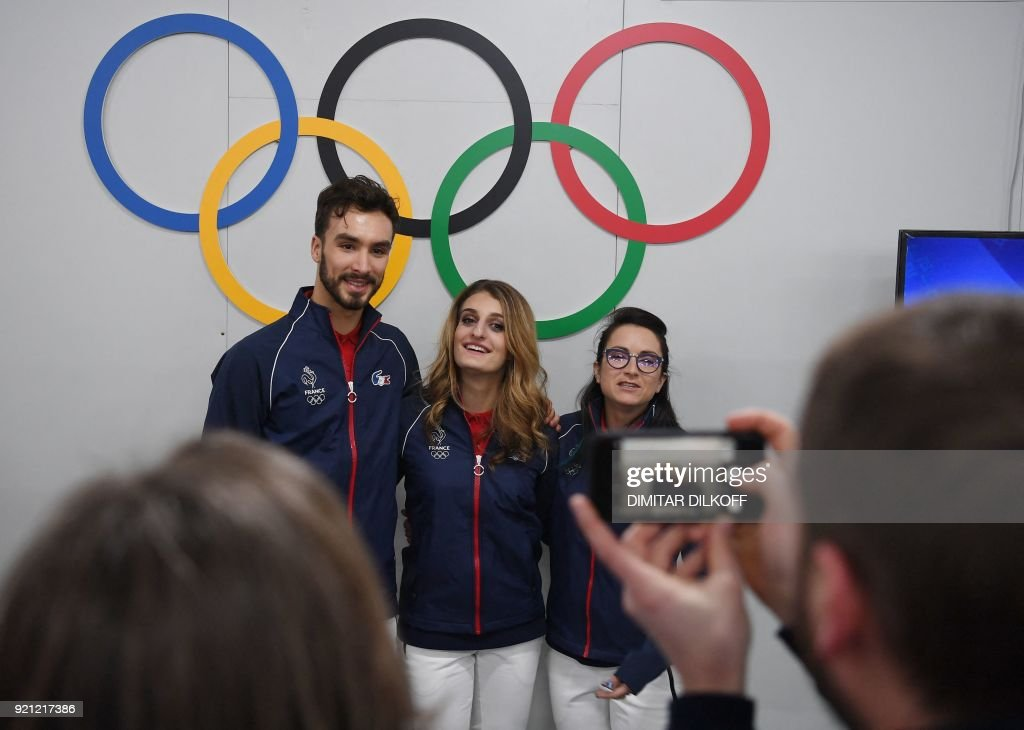 TOPSHOT - France's ice dance silver medallists Gabriella Papadakis (C) and Guillaume Cizeron (L) pose for a picture with France's freestyle skiing halfpipe silver medallist Marie Martinod (R) in front of Olympic rings backstage at the Athletes' Lounge during the medal ceremonies at the Pyeongchang Medals Plaza during the Pyeongchang 2018 Winter Olympic Games in Pyeongchang on February 20, 2018. / AFP PHOTO / Dimitar DILKOFF