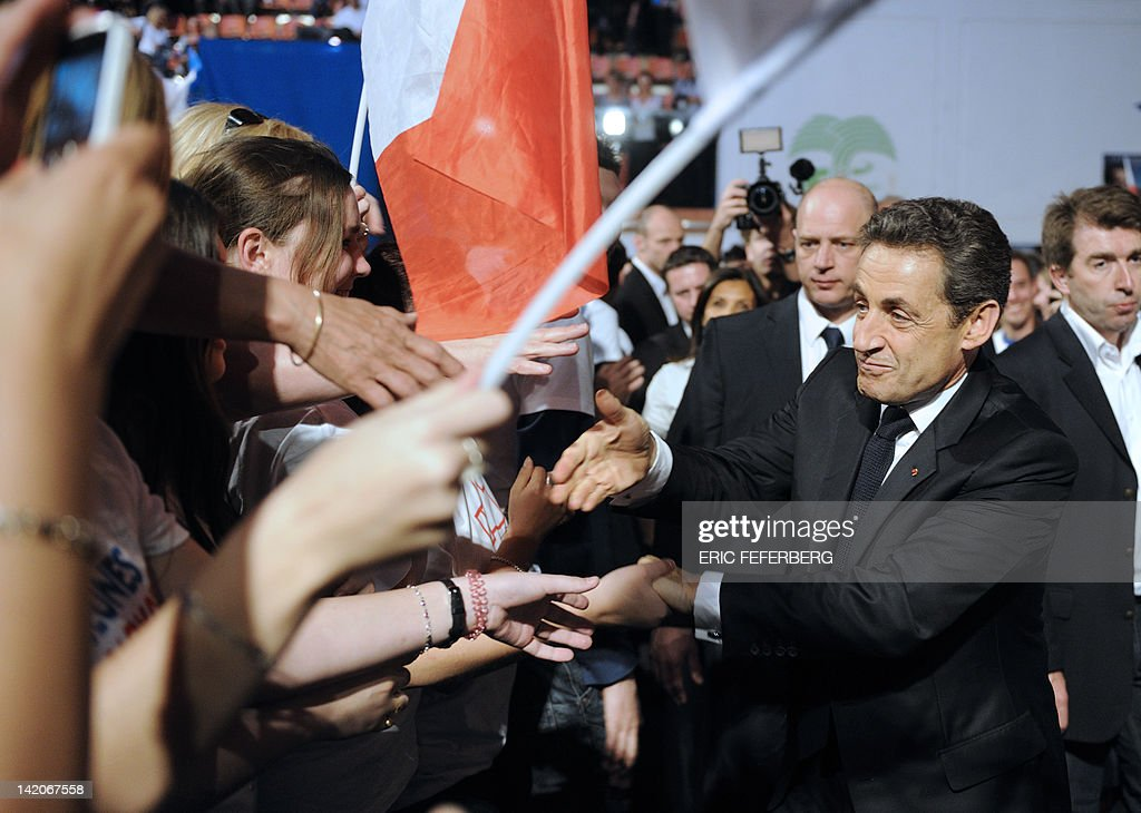 France's incumbent president and Union for a Popular Movement (UMP) party candidate for the French 2012 presidential election Nicolas Sarkozy (R) shakes hands with supporters after delivering a speech during a campaign meeting, on March 29, 2012 in the French southern city of Nimes.