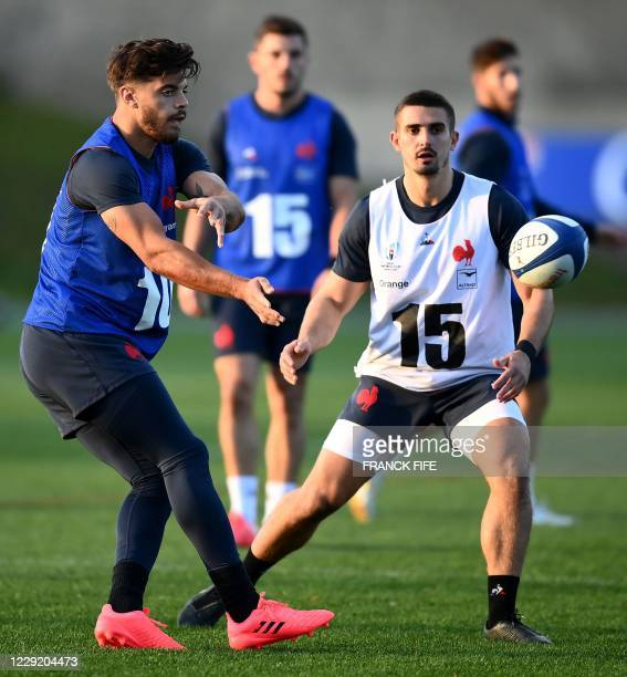 France's inside centre Romain Ntamack passes the ball next to France's full back Teddy Ramos during a training session on October 21 2020 in...