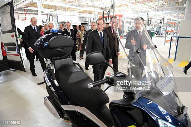 France's Interior Minister Claude Gueant looks at a Gendarmerie motorbike at the vehicle central workshop during his inaugural visit to the...