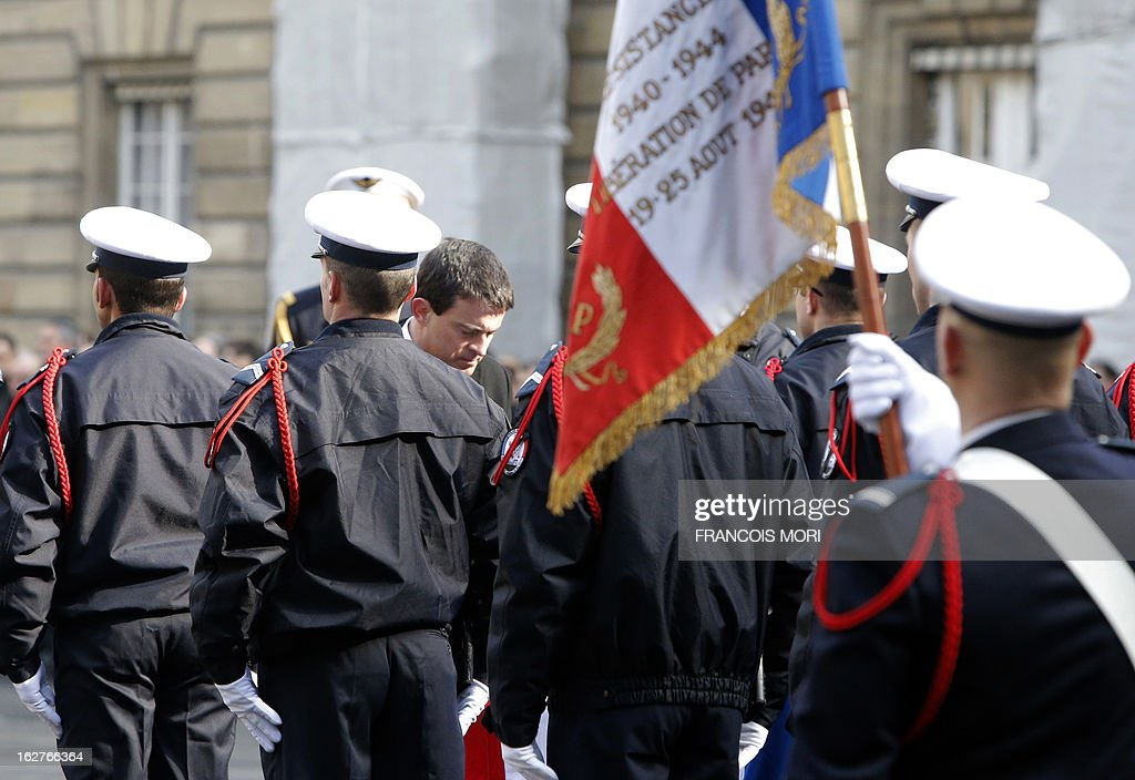 France's Interior Minister Manuel Valls (C) puts awards on the coffins of the two slain policemen, during a ceremony in the yard of the Paris police prefecture, on February 26, 2013 in Paris. An alleged drunk driver killed the two Paris police officers after slamming his black Land Rover into their cruiser during a high-speed chase on the ring road around Paris.