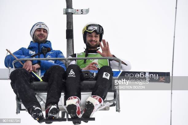 France's Jason LamyChappuis and France's Nordic Combined team head Jerome Laheurte arrive in a lift during the Men's Gundersen of the FIS Nordic...