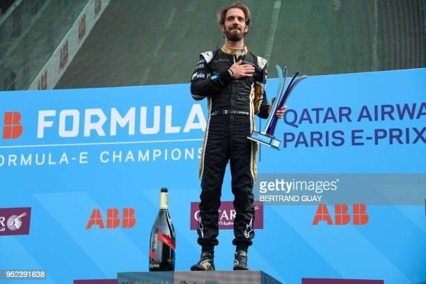 France's Jean-Eric Vergne of the Formula E team Techeetah jubilates on the podium after winning the Paris Formula E championship around The Invalides...