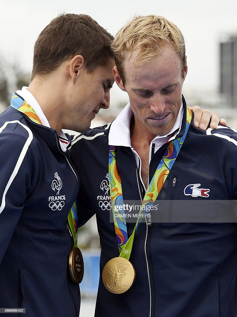 France's Jeremie Azou (R) and France's Pierre Houin cry after receiving their gold medals on the podium of the LWT Men's Double Sculls final rowing competition at the Lagoa stadium during the Rio 2016 Olympic Games in Rio de Janeiro on August 12, 2016. / AFP / Damien MEYER