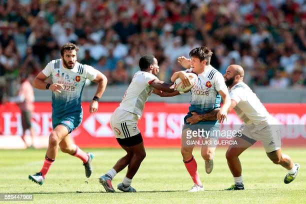 France's Jeremy Aicardi is tackled by Malon Aljibori and Carlin Isles of the US during their match on the second day of the World Rugby Sevens Series...