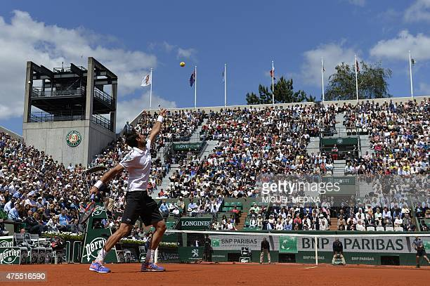 France's Jeremy Chardy serves to Great Britain's Andy Murray during their men's fourth round match at the Roland Garros 2015 French Tennis Open in...