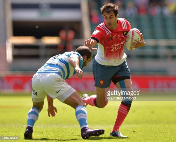 France's Jerome Porical hands off Argentina's Gaston Revol during the group stage match of the World Rugby Sevens Series London rugby union...