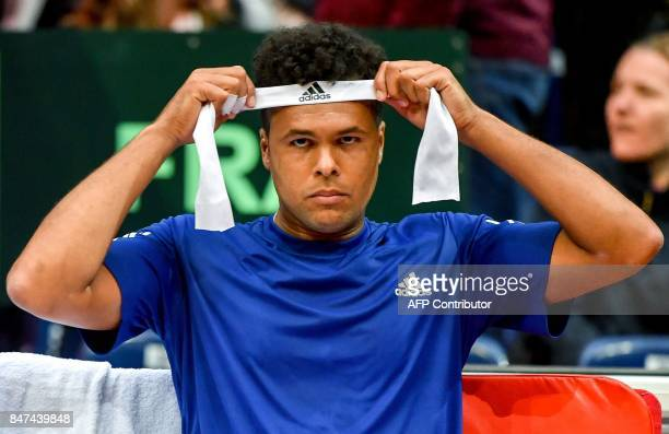 France's Jo-Wilfried Tsonga attaches a head band as he competes against Serbia's Laslo Djere during their singles rubber for the Davis Cup World...