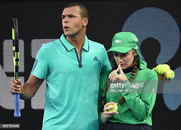 France's JoWilfried Tsonga escorts an ill ballgirl off the court during his men's singles match against Australia's Omar Jasika on day three of the...