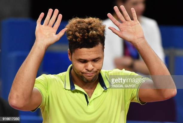 France's JoWilfried Tsonga raises his arms as he withdraws against France's Lucas Pouille during their semi final tennis match at the Open Sud de...
