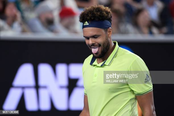 France's JoWilfried Tsonga reacts during their men's singles first round match against Kevin King of the US on day one of the Australian Open tennis...