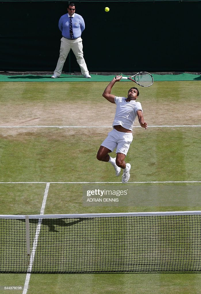TOPSHOT - France's Jo-Wilfried Tsonga returns to US player John Isner during their men's singles third round match on the seventh day of the 2016 Wimbledon Championships at The All England Lawn Tennis Club in Wimbledon, southwest London, on July 3, 2016. / AFP / ADRIAN