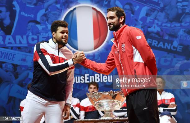 TOPSHOT France's JoWilfried Tsonga shakes hands with Croatia's Marin Cilic next to the Davis Cup trophy during the draw on the eve of the Davis Cup...