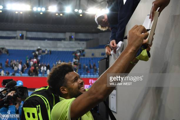 France's JoWilfried Tsonga signs an autograph after beating Kevin King of the US in their men's singles first round match on day one of the...