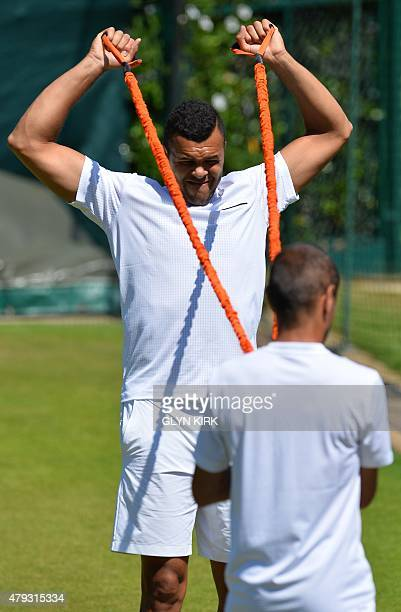 France's JoWilfried Tsonga stretches on the practice court on day five of the 2015 Wimbledon Championships at The All England Tennis Club in...