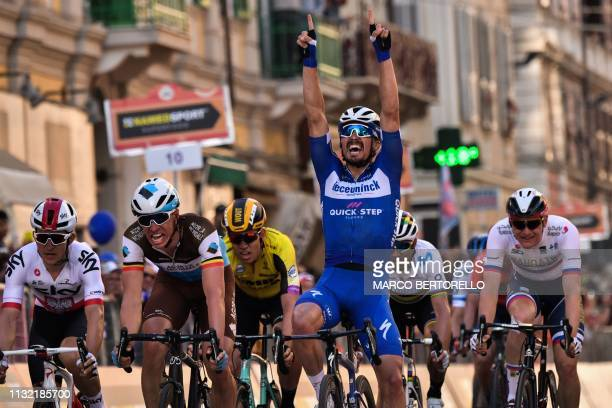 France's Julian Alaphilippe celebrates as he crosses the finish line to win ahead of Belgium's Oliver Naesen and Poland's Michal Kwiatkowski the...