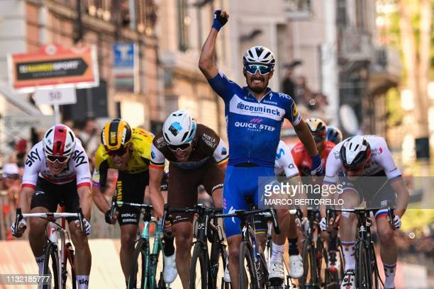 TOPSHOT France's Julian Alaphilippe celebrates as he crosses the finish line to win ahead of Belgium's Oliver Naesen and Poland's Michal Kwiatkowski...