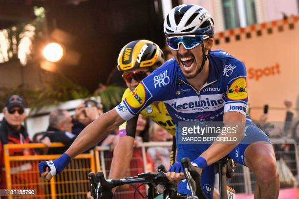 France's Julian Alaphilippe celebrates as he crosses the finish line to win the oneday classic cycling race Milan San Remo on March 23 2019
