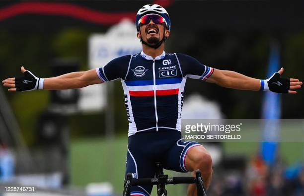 France's Julian Alaphilippe celebrates as he crosses the finish line to win the Men's Elite Road Race, a 258.2-kilometer route around Imola,...