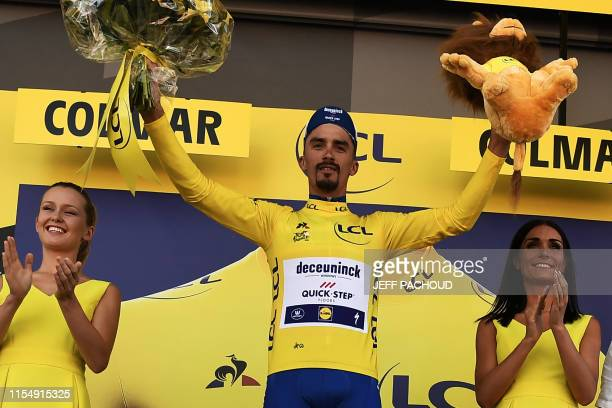 France's Julian Alaphilippe celebrates his overall leader's yellow jersey on the podium of the fifth stage of the 106th edition of the Tour de France...