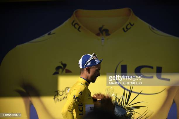 TOPSHOT France's Julian Alaphilippe celebrates his overall leader's yellow jersey on the podium of the ninth stage of the 106th edition of the Tour...