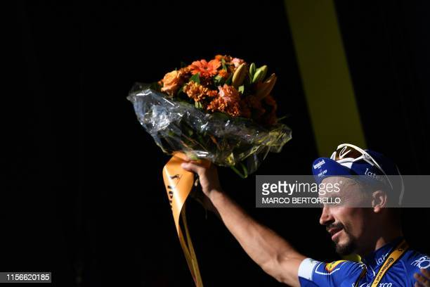 France's Julian Alaphilippe celebrates his overall leader's yellow jersey on the podium of the thirteenth stage of the 106th edition of the Tour de...