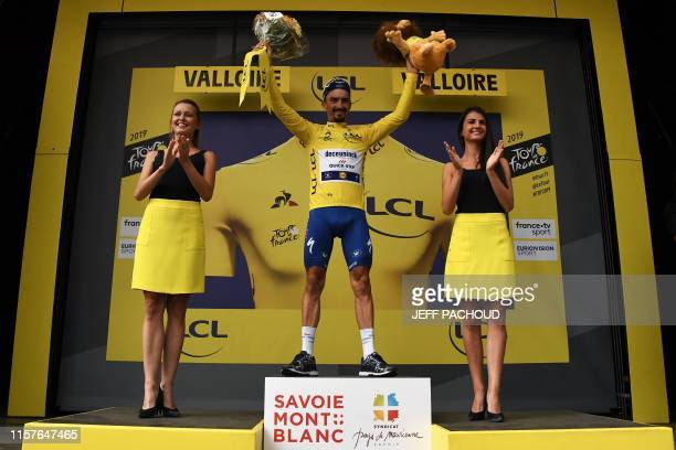 France's Julian Alaphilippe celebrates his overall leader's yellow jersey on the podium of the eighteenth stage of the 106th edition of the Tour de...