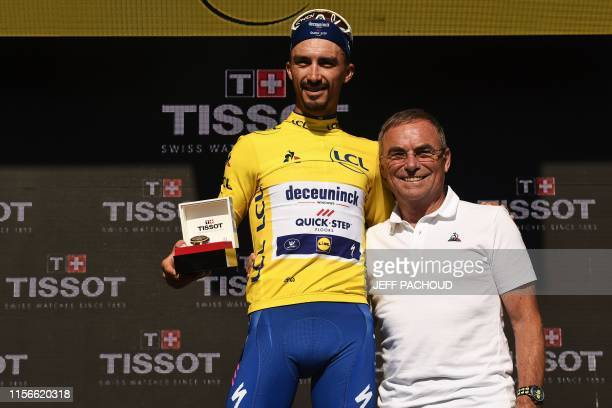France's Julian Alaphilippe poses with former French champion Bernard Hinault as he celebrates his overall leader's yellow jersey on the podium of...