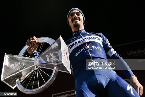 France's Julian Alaphilippe poses with his trophy on the podium after winning the oneday classic cycling race Strade Bianche on March 9 2019 in Siena...