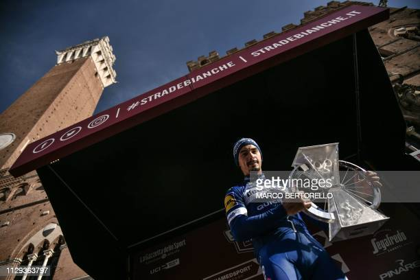 France's Julian Alaphilippe poses with his trophy on the podium, by the Palazzo Pubblico of the medieval square of Piazza del Campo, after winning...