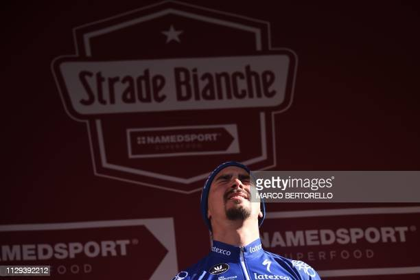 France's Julian Alaphilippe reacts on the podium after winning the one-day classic cycling race Strade Bianche on March 9, 2019 in Siena, Tuscany.
