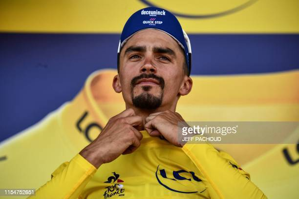 France's Julian Alaphilippe wearing his overall leader's yellow jersey reacts on the podium after the fourth stage of the 106th edition of the Tour...