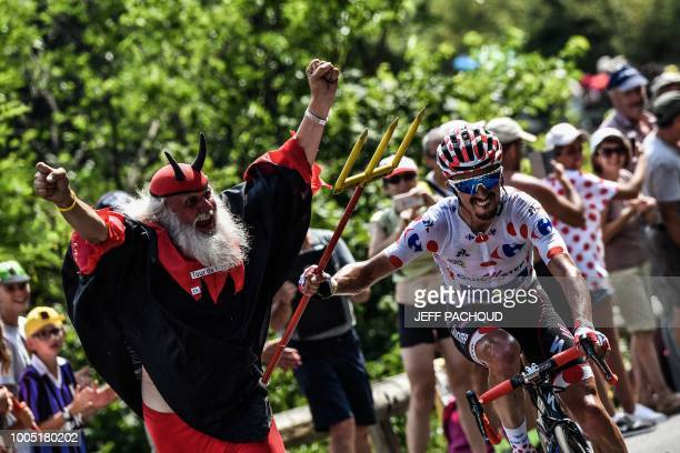 TOPSHOT France's Julian Alaphilippe wearing the best climber's polka dot jersey seizes the fork of Tour de France fan Didi Senft during the 17th...