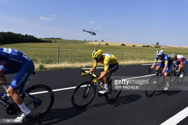 France's Julian Alaphilippe , wearing the overall leader's yellow jersey and cyclists ride as a media helicopter flies in background during the...
