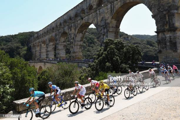 France's Julian Alaphilippe wearing the overall leader's yellow jersey and cyclists cross the Pont du Gard during the sixteenth stage of the 106th...