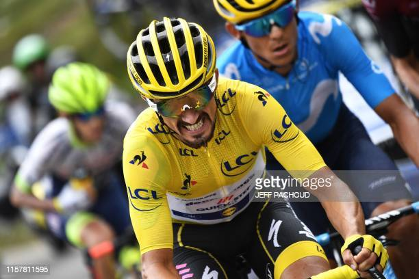 France's Julian Alaphilippe , wearing the overall leader's yellow jersey and cyclists ride uphill during the nineteenth stage of the 106th edition of...