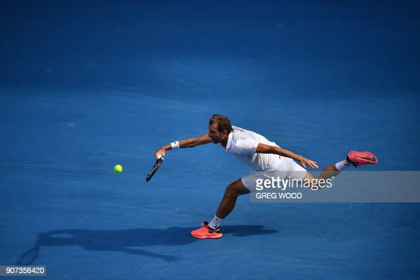 France's Julien Benneteau hits a return against Italy's Fabio Fognini during their men's singles third round match on day six of the Australian Open...