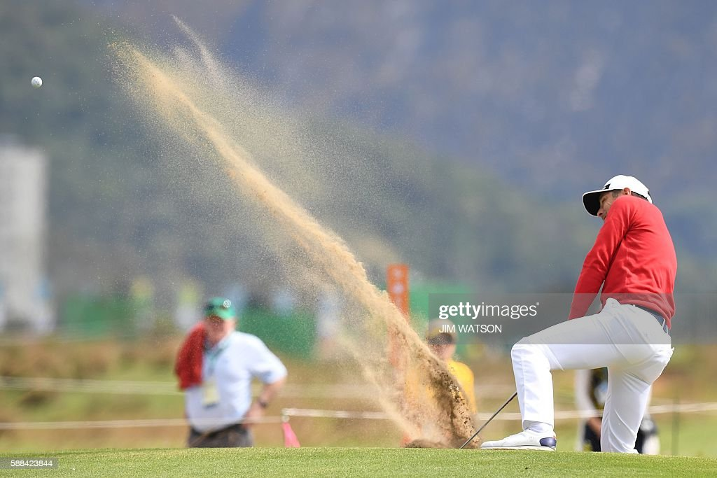 TOPSHOT - France's Julien Quesne shoots out of the bunker during the men's individual stroke play at the Olympic Golf course at the Rio 2016 Olympic Games in Rio de Janeiro on August 11, 2016. / AFP / Jim WATSON