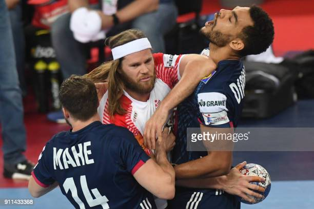 France's Kentin Mahe and France's Adrien Dipanda hold off Denmark's Mikkel Hansen during the match for third place of the Men's 2018 EHF European...