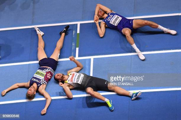 France's Kevin Mayer , Germany's Kai Kazmirek and US athlete Zach Ziemek collapse after the men's 1,000m heptathlon event at the 2018 IAAF World...