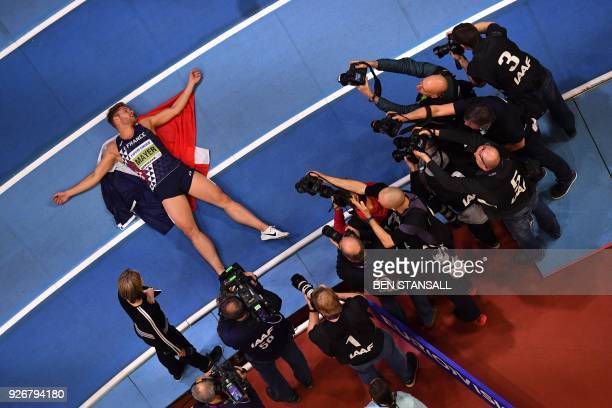 TOPSHOT France's Kevin Mayer lies on the track after taking gold in the men's heptathlon event at the 2018 IAAF World Indoor Athletics Championships...